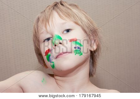 Young boy make selfie with face covered in colourful paint. Kid playing with paints.