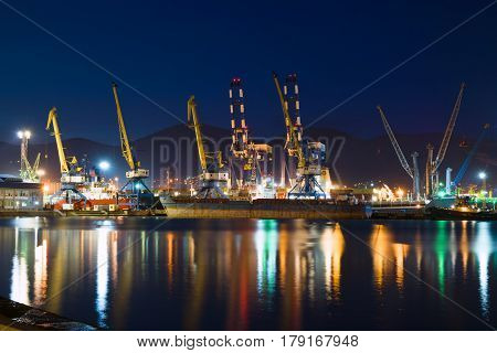 Novorossiysk, Russia - 30, April 2016: Cargo ships in the container terminal. Illuminated cargo port in Novorossiysk at night with container terminals cargo ships and cranes.