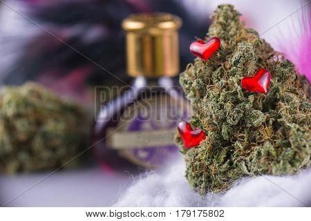 Macro detail of cannabis bud (love potion marijuana strain) with feathers and smoky background