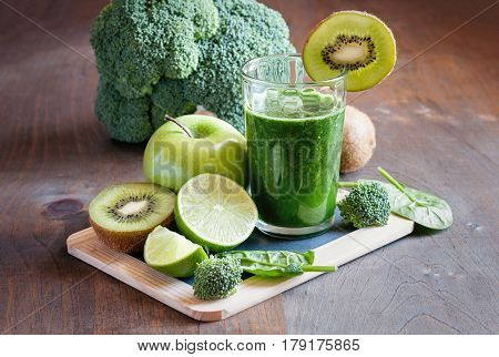 Green fresh spinach smoothie with fruits and veggies lime apples kiwi broccoli. Detox weight loss clean eating vegetarian vegan superfood and healthy diet concept selective focus toned image
