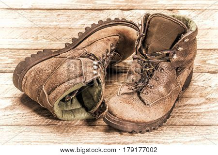 a pair of old, well-worn, hiking boots on weathered wood, retro sepia toning