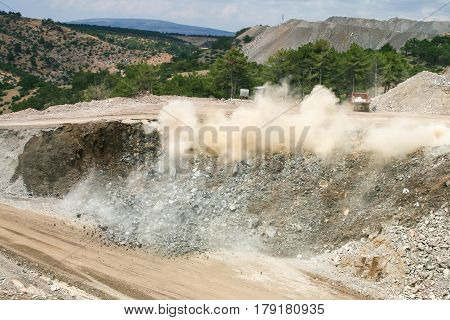open cast mine after blast among dust and smoke