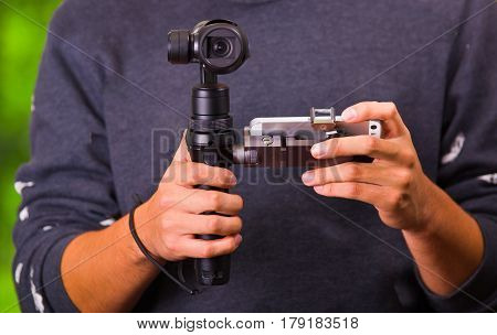 Close up shot of a man using hand held camera stablizer equipment for cell phone