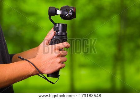 Close up shot of a man using hand held camera stablizer equipment for cell phone outdoors