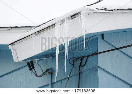 icicle handing from roof near power line