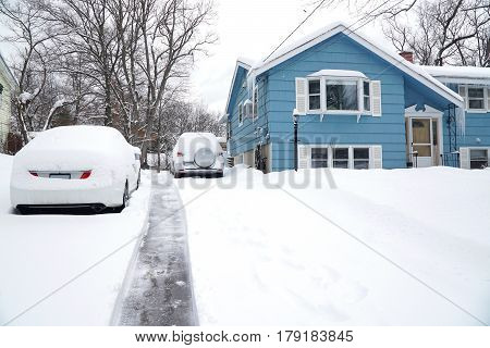 snow removal on driveway after blizzard in residential district