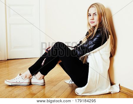 young pretty teenage blond girl sitting on floor at home despair sad alone, lifestyle people concept close up