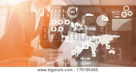Global technology background against businesswoman standing in corridor reading document in office