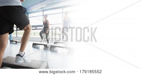 Trainer stepping with aerobics class in gym