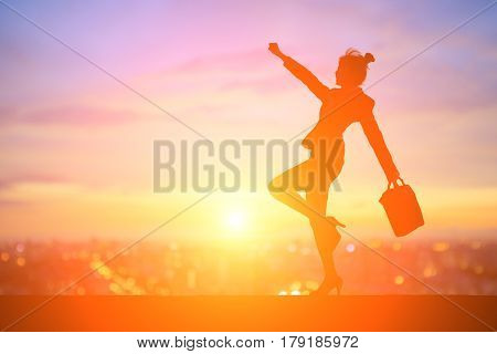 silhouette of business woman feel excited with sunset