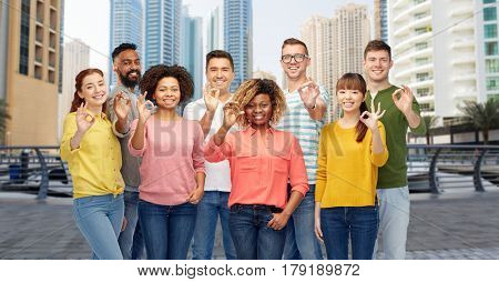 travel, tourism, diversity, ethnicity and people concept - international group of happy smiling men and women showing ok hand sign over dubai city street background