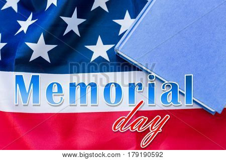 patriotism and national holidays concept - memorial day words over american flag and book