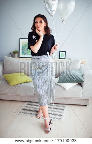 Armenian brunette girl stands in a cozy room on the background of the sofa.