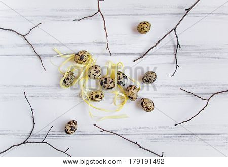 Easter festive background few quail eggs decorated with yellow raffia ribbon on a white vintage wooden table. Flat lay top view minimal concept