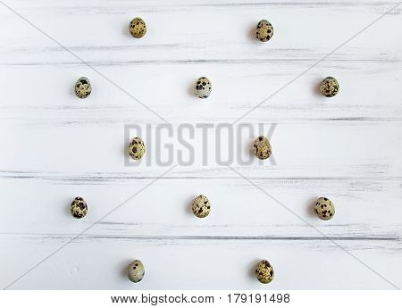 Decorative light pattern with quail eggs on white wooden vintage table. Flat lay top view natural still life eggs polka dot