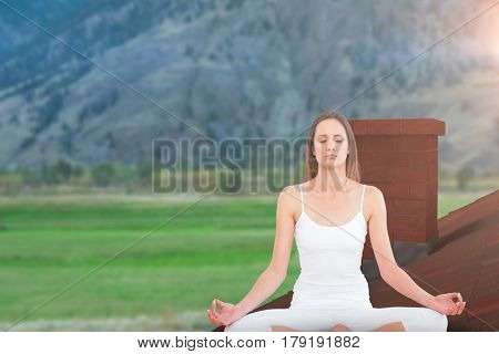 Toned woman in lotus pose at fitness studio against scenic view of green field