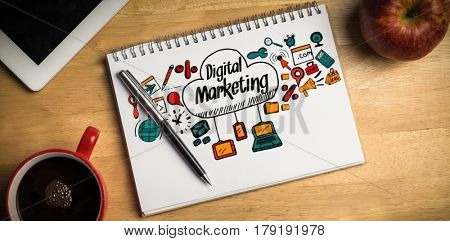 Composite image of digital marketing text with icons against overhead of notepad and pen
