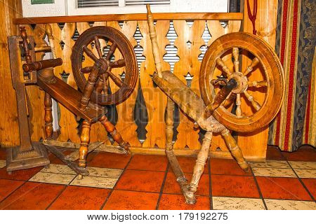 Old retro spinning wheel on wooden background