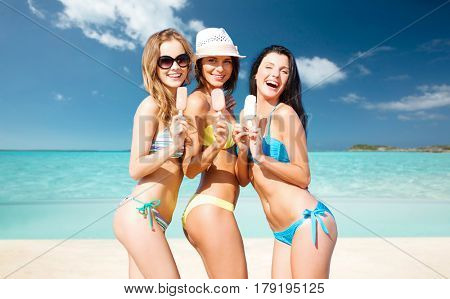 summer holidays, vacation, food, travel and people concept - group of smiling young women eating ice cream over exotic tropical beach background