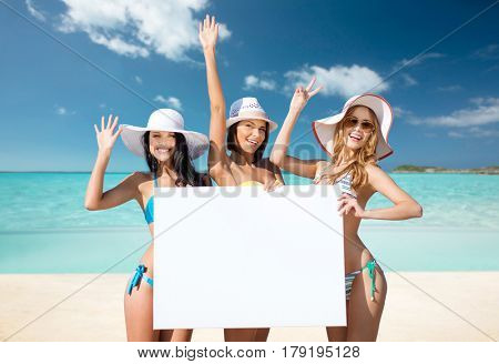 summer holidays, travel, people, advertisement and vacation concept - happy young women in bikinis holding white board over exotic tropical beach background