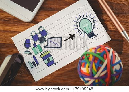 Composite image of computer icons pointing towards light bulb against paper by smartphone and colorful rubber band ball