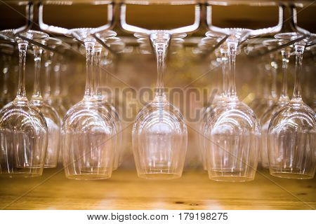 Restaurant bar with empty wine glasses on a rack