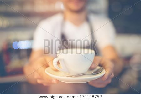 Graphic image of flare against close-up of barista serving coffee at cafeteria