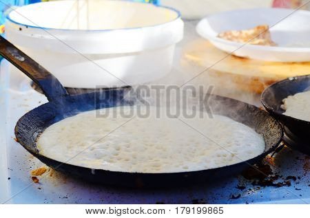 Pancake fried on a hot frying pan steam pan over