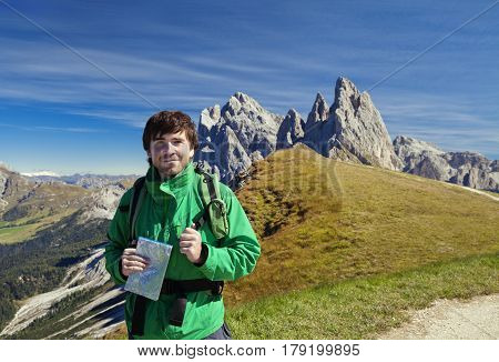 Young tourist in front of Seceda mountain in the Dolomites, Italy