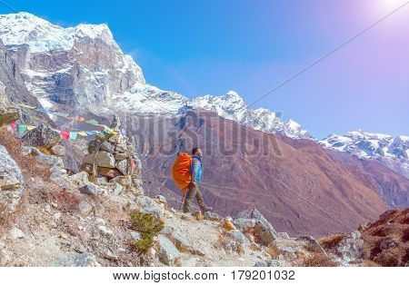 Sunny View of Himalaya Mountains and Nepalese professional Guide in blue Jacket staying on rocky Slope with red Backpack