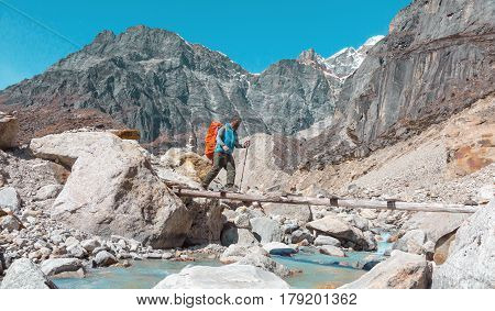 Nepalese Guide in blue Jacket with red Backpack crossing fast Mountain River with pure transparent Water walking on narrow wooden Bridge