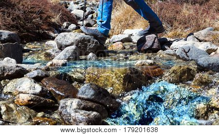 Small clean Mountain Creek with blue pure Water flowing on colourful Watercourse and Hiker in sporty Shoes crossing the River jumping on Stones