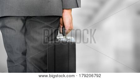 Digital composite of Business person legs with brief case against blurry grey stairs