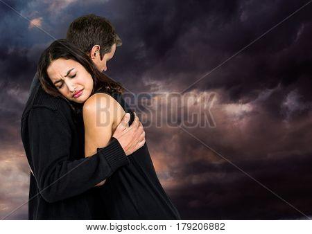 Digital composite of Sad couple hugging against dark cloudy sky