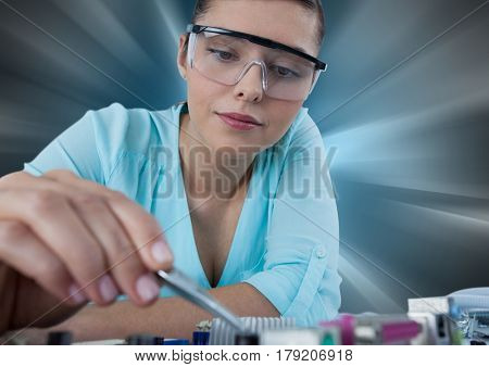 Digital composite of Woman with electronics against motion blur