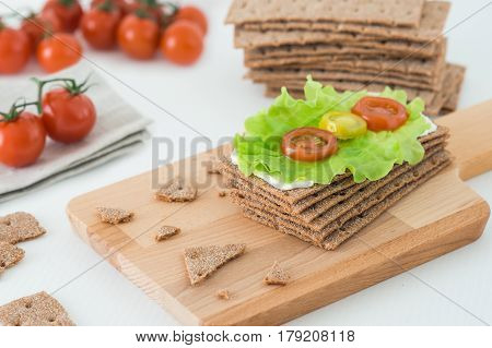 Rye Crispy Bread (swedish Crackers) With Soft Cheese, Lettuce Leave And Cherry Tomatoes On Wooden Bo