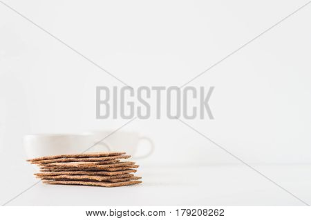 Stacks Of Brown Rye Crispy Bread (swedish Crackers) With Two Cups On White Background With Space For