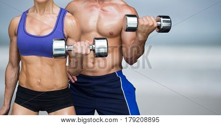 Digital composite of Man and woman weight lifting on blurry beach