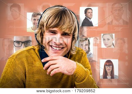 Smiling hipster businessman using headset against orange background