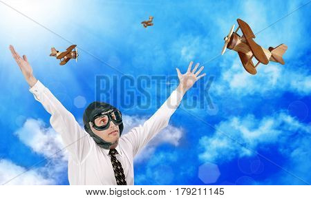 Happy businessman aviator and toy airplanes on a background of blue cloudy sky. Successful business