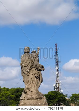 MAJORCA SPAIN - SEPTEMBER 7 2007: Ancient sculpture located on the mountain near monastery San Salvador points to modern telecommunication tower in Majorca Spain on September 7 2007.
