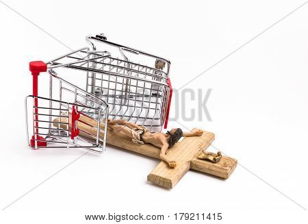 Shopping cart overturned with crucifix on the ground. Conceptual representation of commodification of religion loss of faith blasphemy.