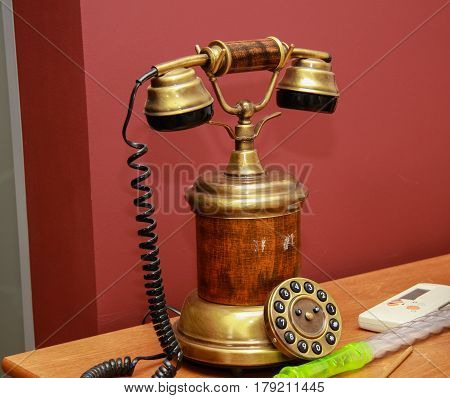 Antique vintage style telephone with dial on wooden shelf