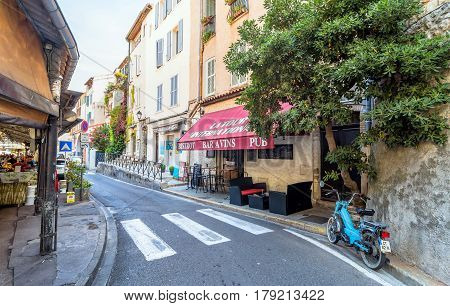 Antibes France - June 29 2016: day view of typical street with bistrot in Antibes France. Antibes is a popular seaside town in the heart of the Cote d'Azur.