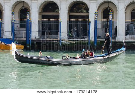 Venice, Italy - February 26th, 2011: tourists travel on gondolas at canal in venice italy
