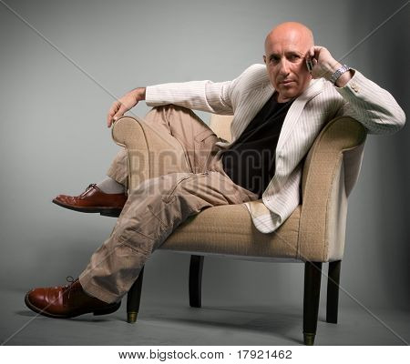 Mature man slumped on an armchair talking on the cell phone