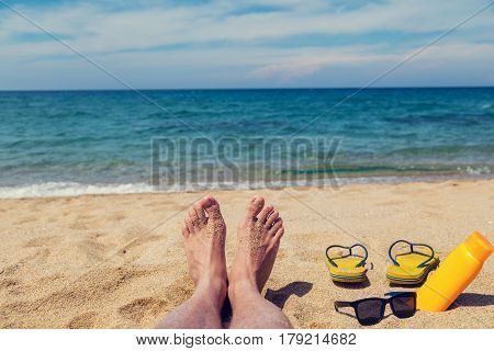 Man sunbathing on the sandy beach. Shallow depth of field on feet and flip flops.