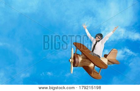 Happy businessman aviator flies in a toy wooden plane against a blue cloudy sky. Successful business