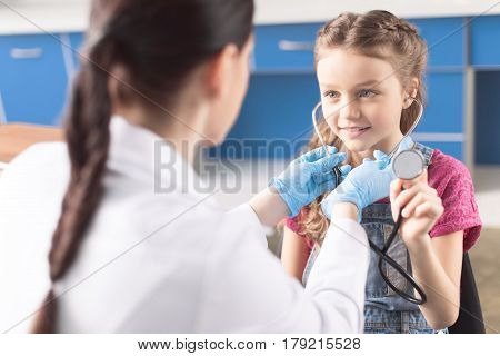 Smiling Little Girl Holding Stethoscope And Looking At Woman Doctor In Hospital