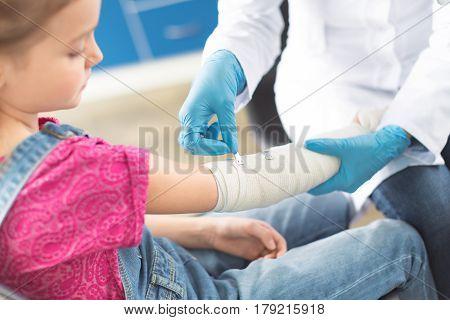 Doctor In White Coat And Medical Gloves Bandaging Hand Of Little Girl